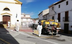 Efectivos del Infoca usan vehículos de extinción para desinfectar una plaza en Marchal.
