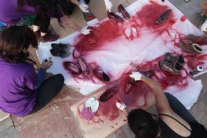 Zapatos teñidos de rojo en un acto contra la violencia machista en la Fuente de las Batallas.