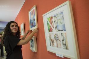 La autora de la muestra, junto a sus obras.