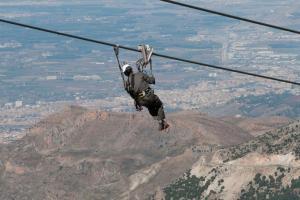 Especialistas colgado del cable de un remonte durante el entrenamiento