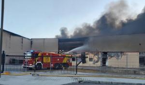 Labores de extinción del fuego en las naves de la empresa.