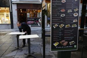 Un empleado acondiciona una terraza de hostelería en Granada capital.