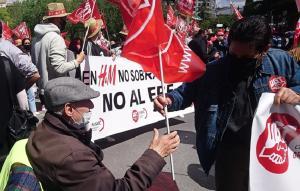Un hombre mayor en silla de ruedas coge una bandera sindical este viernes en la manifestación del Primero de Mayo en Granada.