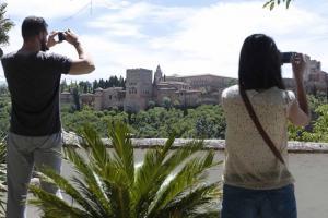 Turistas fotografían la Alhambra en un mirador.