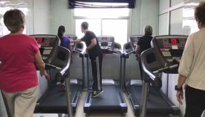 Mujeres realizan ejercicio físico en cintas mecánicas.