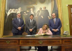 La consejera firma en el libro de honor del Ayuntamiento de Granada en presencia del alcalde, el primer teniente de alcalde y el delegado de la Junta.