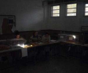 Mesa electoral iluminada con velas.