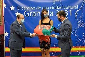 Luis Salvador y Sebastián Pérez entregan la bandera de Granada a la participante en el Miss World Spain.
