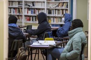 Estudiantes con abrigos recibiendo clases en una imagen de archivo.