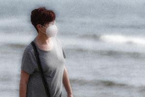 Una mujer con mascarilla pasea por una playa.