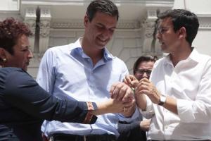 Cuenca, ayudado por Teresa Jiménez, coloca una pulsera de la candidatura socialista a Pedro Sánchez.