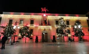 Vista de la Plaza del Carmen con luces navideñas y la fachada del Ayuntamiento iluminada.