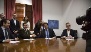 Juan Manuel Moreno y Juan Marín se dan la mano tras la firma en presencia de representantes de su partido.